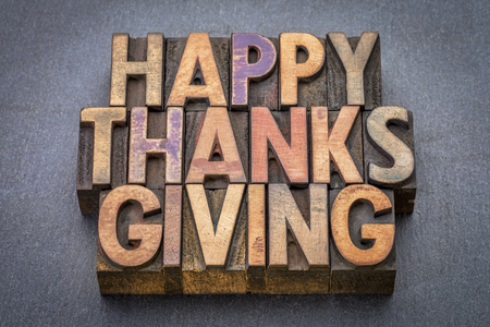 wood type: Happy Thanksgiving greeting card - word abstract in vintage letterpress wood type against slate stone Stock Photo