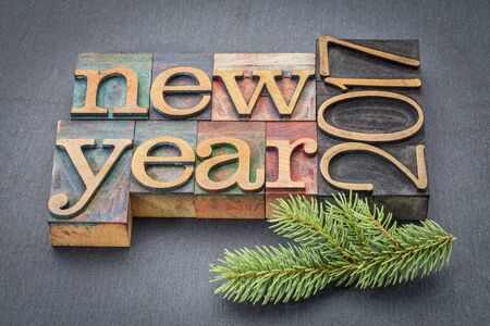 spruce: New Year 2017 greeting card - text in vintage letterpress wood type blocks on a slate stone background with a spruce twig Stock Photo
