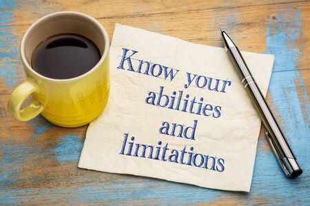 limitations: Know your abilities and limitations - handwriting on a napkin with a cup of espresso coffee Stock Photo