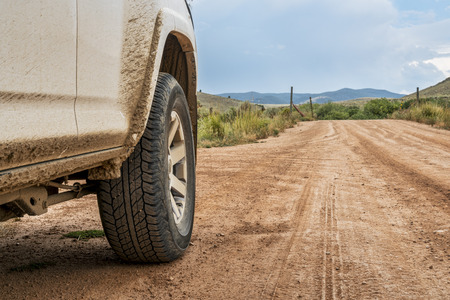 Closeup of 4x4 SUV car driving on a dusty dirt road
