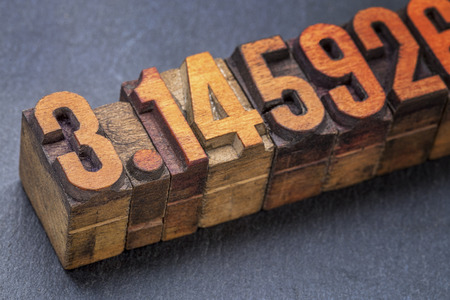 numerical: numerical representation of the pi number - vintage letterpress wood type against a slate stone