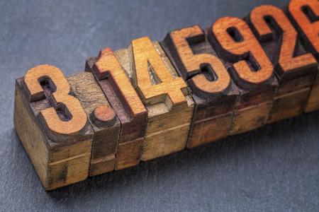 decimal: numerical representation of the pi number - vintage letterpress wood type against a slate stone