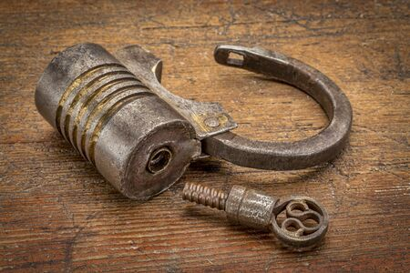 screw key: Vintage round shape hand crafted screw type iron padlock (unlocked) with a key on rustic wood