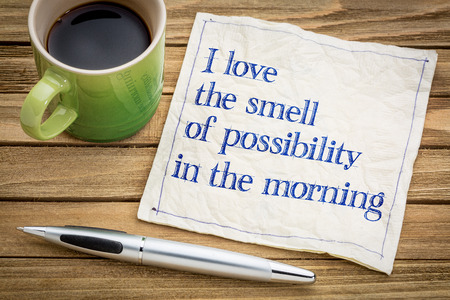 possibility: I love the smell of possibility in the morning - handwriting on a napkin with a cup of espresso coffee Stock Photo