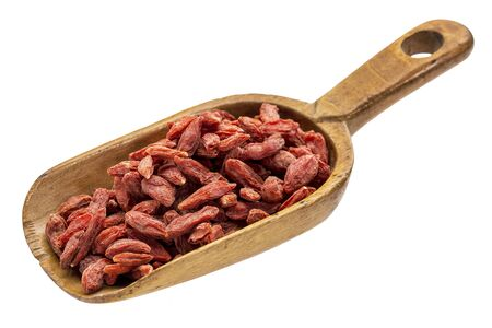 goji berry: dried goji berries on a rustic wooden scoop, isolated on white