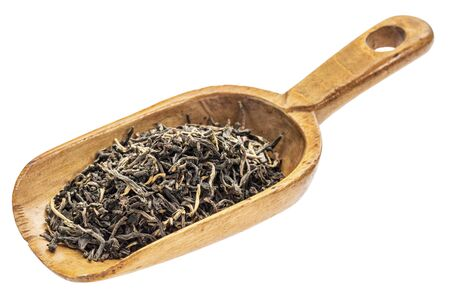 loose leaf: loose leaf black tea on a rustic wooden scoop, isolated on white Stock Photo