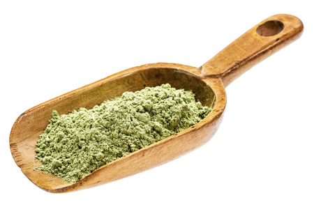 organic barley grass powder on a rustic wooden scoop, isolated on white