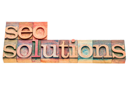 wood type: SEO solutions banner in letterpress wood type printing blocks isolated on white