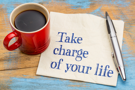 Take charge of your life - handwriting on a napkin with a cup of espresso coffee