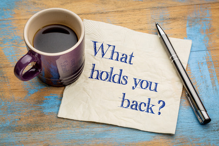 What holds you back? Handwriting on a napkin with a cup of espresso coffee Archivio Fotografico