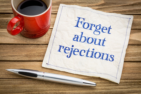 rejections: Forget about rejections - handwriting on a napkin with a cup of espresso coffee Stock Photo