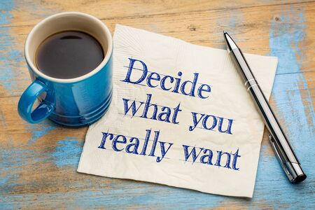 Decide what you really want - handwriting on a napkin with a cup of espresso coffee