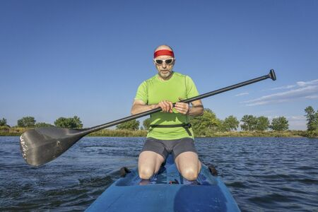 paddler: muscular, senior male paddler on a stand up paddleboard on a lake in Colorado