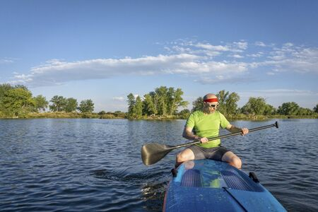 paddler: muscular, senior male paddler sitting on a stand up paddleboard on a lake in Colorado Stock Photo