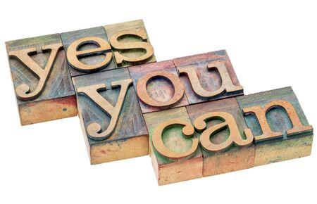 slogan: Sí se puede abstracto de la palabra - lema de motivación en el tipo de madera de cosecha, aislado en blanco