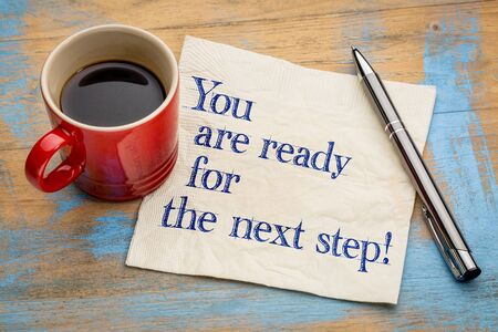 the next step: You are ready for the next step! Handwriting on a napkin with a cup of espresso coffee