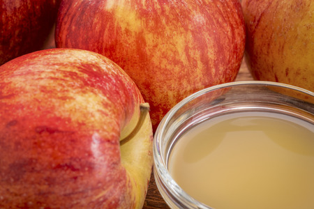 unfiltered: unfiltered, raw apple cider vinegar with mother - a small galls bowl surrounded by fresh red apples