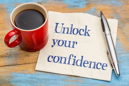 self image: Unlock your confidence advice  or reminder - handwriting on a napkin with a cup of espresso coffee Stock Photo