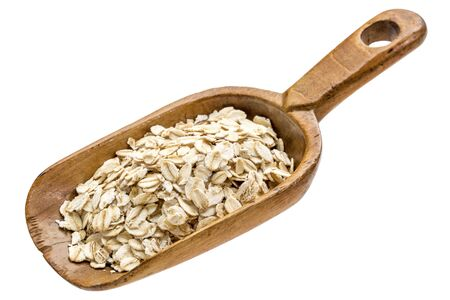 rolled oats: gluten free, organic rolled oats on a rustic wooden scoop isolated on white Foto de archivo