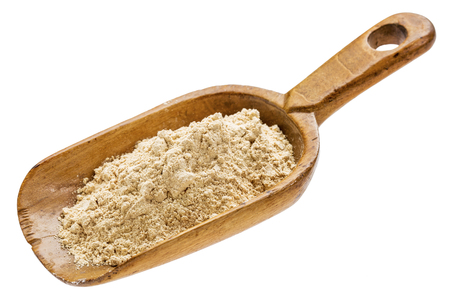 maca root powder on  a rustic wooden scoop isolated on white Banco de Imagens