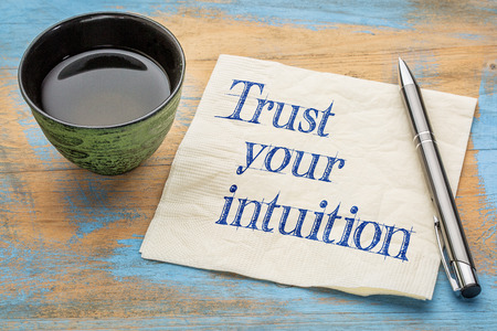 instinct: Trust your intuition reminder - handwriting on a napkin with a cup of tea