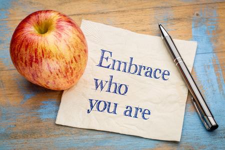 Umfassen Sie, wer Sie sind - Handschrift auf eine Serviette mit einem frischen Apfel