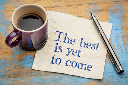 The best is yet to come - handwriting on a napkin with a cup of espresso coffee