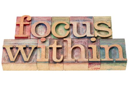introspection: focus within word abstract - isolated text in letterpress wood type printing blocks stained by color inks