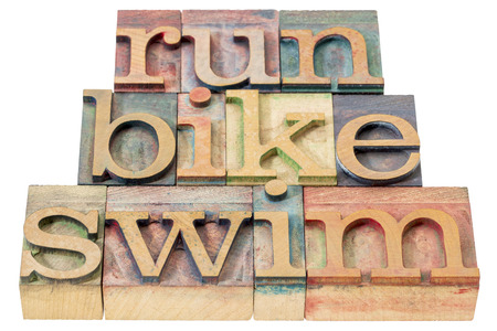 wood type: run, bike, swim - triathlon concept - isolated word abstract in letterpress wood type printing blocks