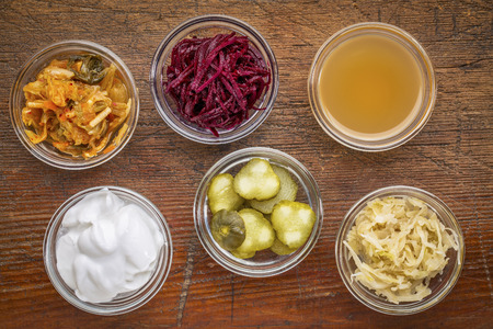 a set of fermented food great for gut health - top view of glass bowls against wood:  kimchi, red beets, apple cider vinegar, coconut milk yogurt, cucumber pickles, sauerkraut