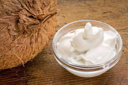 yogurt: yogur de leche de coco - un pequeño tazón de vidrio contra la madera rústica con un coco Foto de archivo