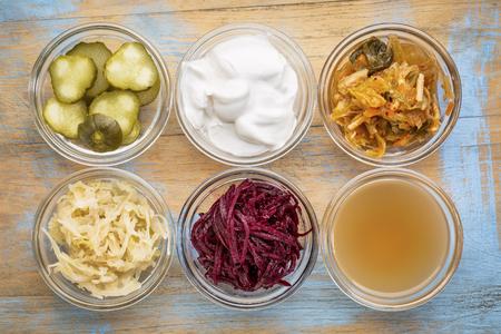 Un ensemble d'aliments fermentés excellent pour la santé de l'intestin - vue de dessus des bols en verre contre le bois grunge: cornichons, yaourt au lait de coco, le kimchi, la choucroute, les betteraves rouges, vinaigre de cidre Banque d'images - 63293945