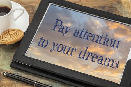 poner atencion: Prestar atención a sus sueños - texto inspirado en una tableta digital con una taza de café