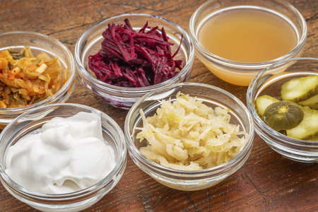 a sampler of fermented food great for gut health - glass bowls against wood:  kimchi, red beets, apple cider vinegar, coconut milk yogurt, cucumber pickles, sauerkraut Stock Photo