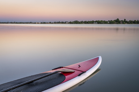 loveland: stand up paddleboard with a paddle on calm lake at dusk in northern Colorado