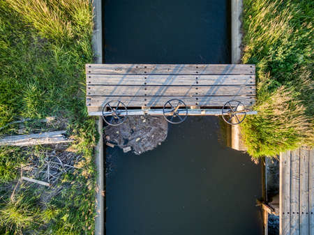 photgraphy: aerial view of irrigation ditch with gates and footbridge in Colorado