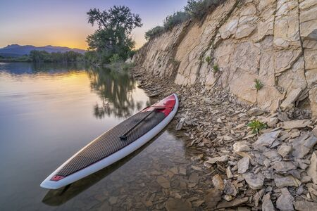 loveland: stand up paddleboard with a paddle on calm lake with a rocky cliff at dusk in northern Colorado
