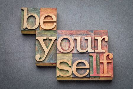 printing block block: be yourself word abstract in letterpress wood type blocks against gray slate stone Stock Photo