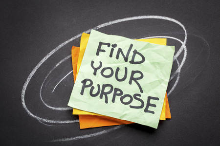 find your purpose  - motivational reminder - handwriting on a sticky note against black paper Stock Photo