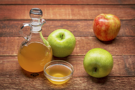 unfiltered, raw apple cider vinegar with mother - a cruet with a small glass  bowl surrounded by fresh  apples on rustic wood Standard-Bild