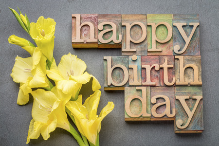 happy birthday greeting card - word abstract in letterpress wood type with a yellow gladiola flower against gray slate stone background Foto de archivo