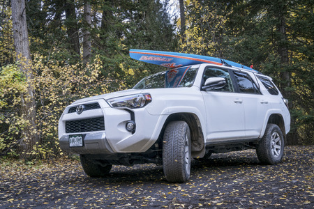 dirt road recreation: CRYSTAL, CO, USA - SEPTEMBER 28, 2016: Toyota 4Runner SUV (2016 Trail edition) carrying  a paddleboard on a back country road in Colorados Rocky Mountains