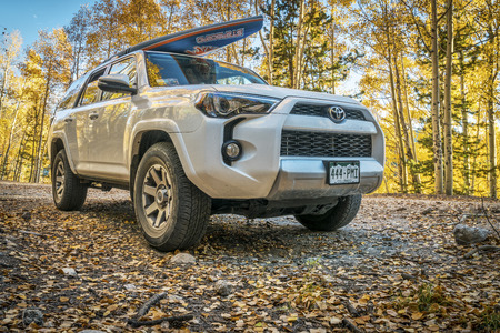 dirt road recreation: BASALT, CO, USA - SEPTEMBER 27, 2016: Toyota 4Runner SUV (2016 Trail edition) carrying  a paddleboard on Frying Pan Road with fall colors in Colorados Rocky Mountains