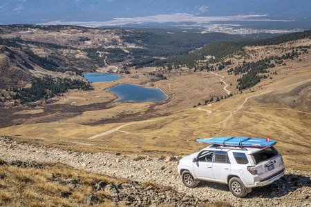 dirt road recreation: LEADVILLE, CO, USA - SEPTEMBER 27, 2016: Toyota 4Runner SUV (2016 Trail edition) with a paddleboard descending  from the Mosquito Pass on a rocky jeep trail in Colorados Rocky Mountains
