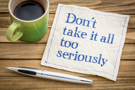 humilde: Do not take it all too seriously - handwriting on a napkin with a cup of espresso coffee