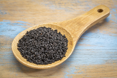 nigella seeds: black cumin seeds (Nigella sativa) on a wooden spoon Stock Photo