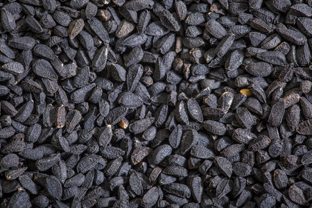 nigella seeds: black cumin seeds (Nigella sativa) - closeup background