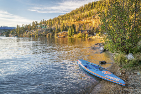 starboard: GRAND LAKE,  CO, USA - SEPTEMBER 26: All Star racing stand up paddleboard by Starboard in brushed carbon layout with Werner paddle on a shore of Grand Lake.