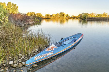 FORT COLLINS  CO, USA - OCTOBER 7, 2016: All Star racing stand up paddleboard by Starboard in brushed carbon layout with Werner paddle on a shore of a local lake with fall colors. Editorial