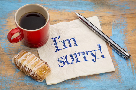 i am sorry: Im sorry - handwriting on a  napkin with a pen,cup of espresso coffee and cookie against grunge painted wood Stock Photo